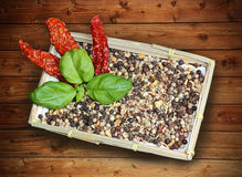 Basket with mixed hot pepper spices, basil and dried chillies Royalty Free Stock Image