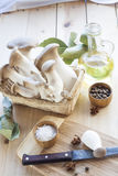 Basket with mushrooms, olive oil and ingredients for cooking on the wooden table of the kitchen background Stock Image