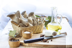 Basket with mushrooms, olive oil and ingredients for cooking on the wooden table of the kitchen background Stock Photo