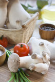 Basket with mushrooms, olive oil and ingredients for cooking on the wooden table of the kitchen background Royalty Free Stock Images