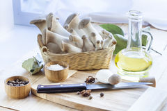 Basket with mushrooms, olive oil and ingredients for cooking on the wooden table of the kitchen background Stock Photography