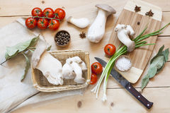 Basket with mushrooms, olive oil and ingredients for cooking on the wooden table of the kitchen background Stock Images