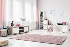 Drapes in spacious pink bedroom. Basket next to a wooden cupboard in spacious bedroom interior with pink drapes and carpet Stock Photo
