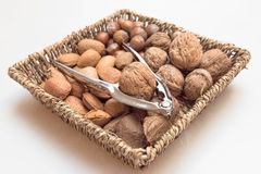 Basket with nuts and nutcracker. A basket with walnuts, Almonds, Brazil nuts, hazel nuts and a nut cracker stock photography