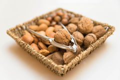 Basket with nuts. A basket with walnuts, Almonds, Brazil nuts, hazel nuts and a nut cracker stock photography