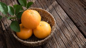 Basket of orange fruit set on wood table Stock Photo