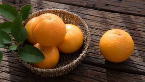 Basket of orange fruit set on wood table Royalty Free Stock Photo