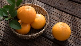 Basket of orange fruit set on wood table Royalty Free Stock Photography