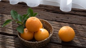 Basket of orange fruit set on wood table Stock Photos
