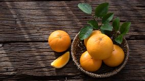 Basket of orange fruit set on wood table Stock Images