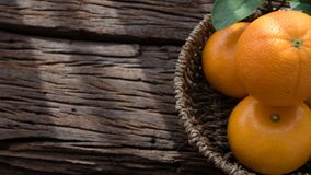 Basket of orange fruit set on wood table Royalty Free Stock Photos