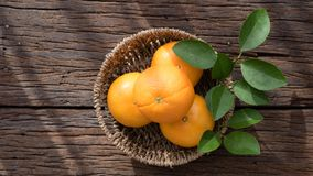 Basket of orange fruit set on wood table Royalty Free Stock Image