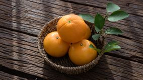 Basket of orange fruit set on wood table Stock Image