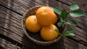 Basket of orange fruit set on wood table Royalty Free Stock Images