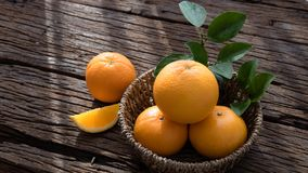 Basket of orange fruit set on wood table Stock Photography