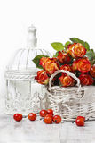 Basket of orange roses and white victorian birdcage. On white background Royalty Free Stock Images