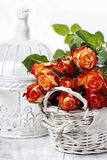 Basket of orange roses and white victorian birdcage. On white background Royalty Free Stock Photography