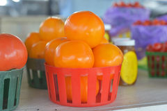 Basket Of Orange Tomatoes. For sale at a roadside fruit and vegetable stand stock image