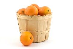 Basket of oranges. Wooden basket of ripe oranges isolated on white background Stock Photos
