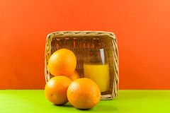 Basket with oranges. Glass of juice with oranges on red background stock photo