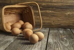 Basket with organic eggs on a weathered table. Royalty Free Stock Photography