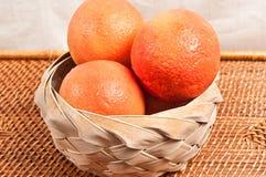 Basket of organic grapefruits. Weaved reed basket of organic, ripe, fresh, juicy Royalty Free Stock Photo