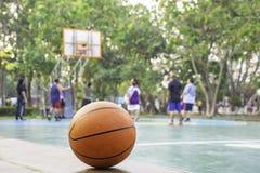 Basket på den oskarpa bilden för trästolbakgrund av folk som spelar basket på en domstol royaltyfri foto