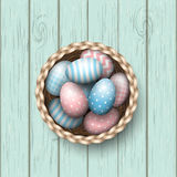 Basket with painted easter eggs on blue wooden background, illustration royalty free illustration