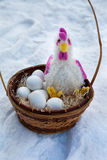 Basket with paraphernalia on Easter, rooster and Easter eggs lying in basket in the snow Stock Photography