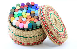Basket of Pastel Crayons. Woven basket, with lid, filled with assorted colorful pastel crayons; white background. Concept for art and creativity as well as stock photo