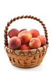 Basket of peaches. Basket full of fresh peaches isolated on white Royalty Free Stock Images