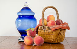 Basket of peaches and blue jar Stock Image