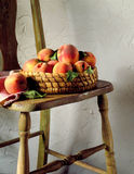 Basket of peaches on chair. Fresh peaches in basket on wood chair Royalty Free Stock Photography