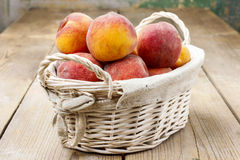 Basket of peaches on wooden table Stock Photography