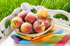 Basket of peaches on wooden tray Stock Photo