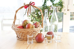 A basket with pears and pear schnapps Stock Photo