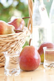 A basket with pears and pear schnapps Stock Photos
