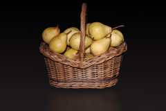 Basket with pears on pure black background. Royalty Free Stock Image