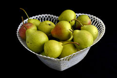 Basket of pears. White basket with pears on a black background Stock Photos