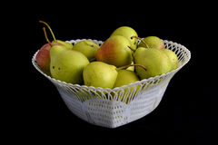Basket of pears. White basket with pears on a black background Royalty Free Stock Photography