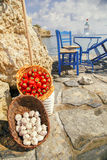 Basket with pepper and garlic on a background of sea and rocks. Royalty Free Stock Photography