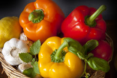 Basket with peppers, garlic, lemon and herbs Stock Images