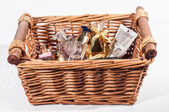 A Basket of Perfumes and Beauty Care Products. A wooden wicker basket containing various cosmetic, perfume and beauty care products isolate on a white background royalty free stock image