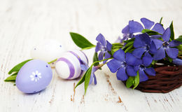 Basket with  periwinkle and easter eggs. Basket with beautiful blue periwinkle and easter eggs Stock Photo