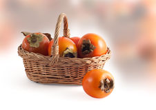 Basket with a persimmon Royalty Free Stock Image