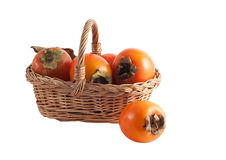 Basket with a persimmon Stock Photos