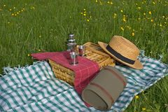 Basket of picnic. In grass posed on a tablecloth with a hat Stock Photography