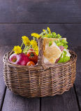 Basket for picnic with a sandwich, apple, tomatoes and flowers.  Stock Photo