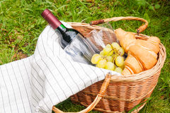 Basket for picnic with wine, croissants, grape and picnic blanket Royalty Free Stock Photos