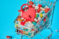 Basket of pills and red heart-shaped padlock. Blue background. Concept: a Healthy heart. Pharmaceuticals and medicine prolong life. Copy space for text Stock Photography